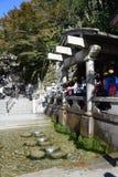 Turistas no identificados que recogen el agua de la Otowa-ninguna-taki cascada en el templo de Kiyomizu, Kyoto Fotografía de archivo