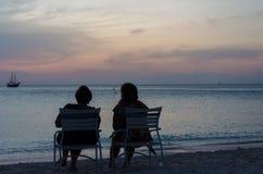 Turistas no por do sol com os barcos de vela ancorados Foto de Stock Royalty Free