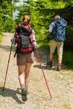 Turistas novos com os polos trekking nas madeiras Fotos de Stock Royalty Free