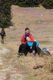 Turistas novos que sentam-se no prado da montanha Fotografia de Stock
