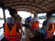 Turistas occidentales en el barco del viaje en el delta Vietnam del río Mekong Fotos de archivo