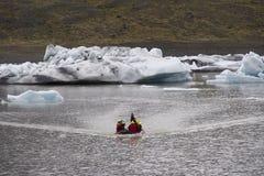 Turistas perto do gelo congelado da geleira em Islândia foto de stock