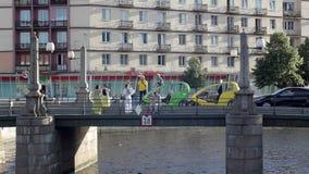 Turistas perto do táxi da bicicleta na ponte sobre o canal de rio em St Petersburg vídeos de arquivo