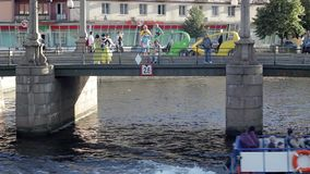 Turistas perto do táxi da bicicleta na ponte sobre o canal do rio com um barco de prazer no Sa vídeos de arquivo