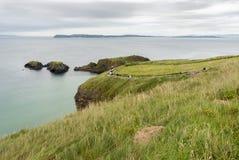 Turistas que andam à ponte de corda - Irlanda do Norte Imagens de Stock Royalty Free