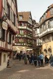 Turistas que andam através das ruas na cidade mediaval velha de Colmar foto de stock