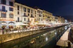 Turistas que andam dentro pelo canal grandioso de Naviglio no distrito de Navigli, Milão, Itália Fotografia de Stock