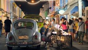 Turistas que andam e que compram na rua velha completamente dos vendedores locais que vendem o alimento e a roupa domingo à noite filme