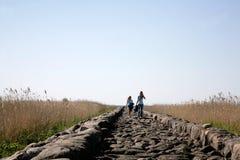 Turistas que andam na estrada Fotos de Stock Royalty Free