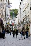 Turistas que andam pela rua de Getreidegasse no centro histórico de Salzburg Imagem de Stock Royalty Free