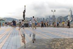 Turistas que andam perto da estátua de bronze de Hong Kong Film Awards e da skyline na avenida das estrelas Imagens de Stock Royalty Free