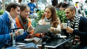 Turistas que bebem o café no café e que leem o mapa da cidade imagens de stock