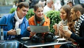 Turistas que beben el café en el café y que leen el mapa de la ciudad Fotos de archivo libres de regalías