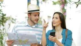 Turistas que buscan ubicaciones con el teléfono y el mapa