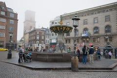 Turistas que caminan cerca de la fuente del día brumoso de noviembre de la misericordia copenhague Imágenes de archivo libres de regalías