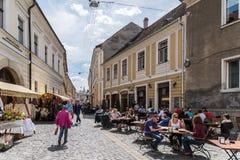 Turistas que caminan en el centro de la ciudad en el viejo centro de Cluj Napoca Imágenes de archivo libres de regalías