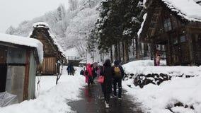 Turistas que caminan en el pueblo histórico durante nevar en la estación del invierno