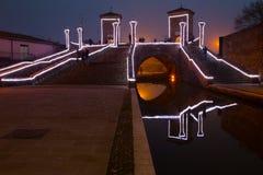Turistas que caminan en el puente Trepponti, Comacchio, Italia por noche imagenes de archivo