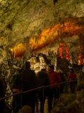 Turistas que caminan en la trayectoria entre las estalactitas y las estalagmitas iluminadas Imagen de archivo libre de regalías