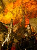 Turistas que caminan en la trayectoria entre las estalactitas y las estalagmitas iluminadas Foto de archivo