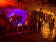 Turistas que caminan en la trayectoria entre las estalactitas y las estalagmitas iluminadas Fotos de archivo libres de regalías