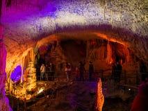 Turistas que caminan en la trayectoria entre las estalactitas y las estalagmitas iluminadas Imagen de archivo