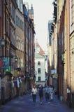 Turistas que caminan en las calles viejas del adoquín en el mercado en Gamla Stan, la ciudad vieja de Estocolmo en Suecia Imagen de archivo libre de regalías