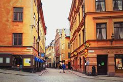 Turistas que caminan en las calles viejas del adoquín en el mercado en Gamla Stan, la ciudad vieja de Estocolmo en Suecia Fotografía de archivo