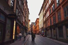 Turistas que caminan en las calles viejas del adoquín en el mercado en Gamla Stan, la ciudad vieja de Estocolmo en Suecia Fotos de archivo