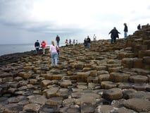 Turistas que caminan en las columnas del basalto del terraplén del gigante Foto de archivo libre de regalías