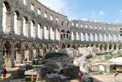 Turistas que caminan en las ruinas del amphitheatre romano en las pulas Fotos de archivo libres de regalías