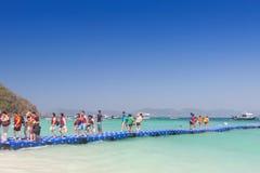 Turistas que caminan en pontón azul a la playa en Coral Island P foto de archivo libre de regalías