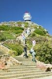 Turistas que caminan encima de los pasos que llevan al faro viejo del punto del cabo en el punto del cabo fuera de Cape Town, Sur Foto de archivo