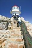 Turistas que caminan encima de los pasos que llevan al faro viejo del punto del cabo en el punto del cabo fuera de Cape Town, Sur Foto de archivo libre de regalías