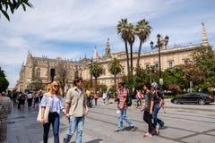 Turistas que caminan a lo largo de la calle cerca de la catedral de Sevilla imágenes de archivo libres de regalías