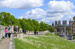 Turistas que caminan a lo largo de la pared romana de la ciudad de York que rodea la ciudad Fotografía de archivo