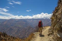 Turistas que caminan a lo largo de la trayectoria en las montañas Imagen de archivo