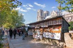 Turistas que caminan por las cajas del librero famoso (bouquinistes) a lo largo del río Sena cerca de Notre Dame en París Fotografía de archivo libre de regalías