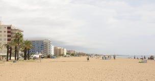 Turistas que caminan y que toman el sol en la playa Fotografía de archivo