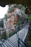 Turistas que caminham na fuga íngreme do ziguezague da escadaria grande ao longo do penhasco vermelho da tesoura da rocha com veg foto de stock royalty free