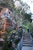 Turistas que caminham na fuga íngreme do ziguezague da escadaria grande ao longo do penhasco vermelho da tesoura da rocha com veg imagens de stock royalty free