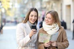Turistas que comparan el teléfono y el mapa en vacaciones de invierno fotografía de archivo