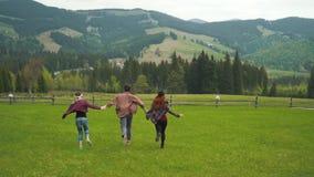 Turistas que corren llevando a cabo las manos en valle de las montañas almacen de video