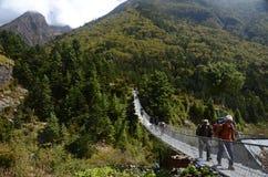 Turistas que cruzam uma ponte nos Himalayas Imagens de Stock Royalty Free