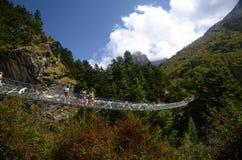 Turistas que cruzan un puente en el Himalaya Imagen de archivo libre de regalías