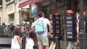 Turistas que dan un paseo en recuerdos de las compras de la calle de París y pequeñas tiendas que visitan