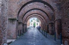 Turistas que dan un paseo a través de las calles históricas antiguas de Roma debajo de los arcos de piedra en el área en la igles imágenes de archivo libres de regalías