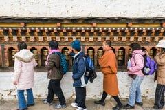 Turistas que dan vuelta a las ruedas de rezo Foto de archivo libre de regalías