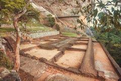 Turistas que descienden de la montaña en la ciudad antigua de Sigiriya con ruinas y área arqueológica Imágenes de archivo libres de regalías