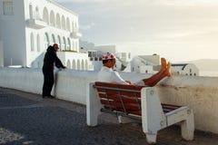 Turistas que disfrutan de la puesta del sol en un banco en la ciudad blanca de Fira fotografía de archivo libre de regalías